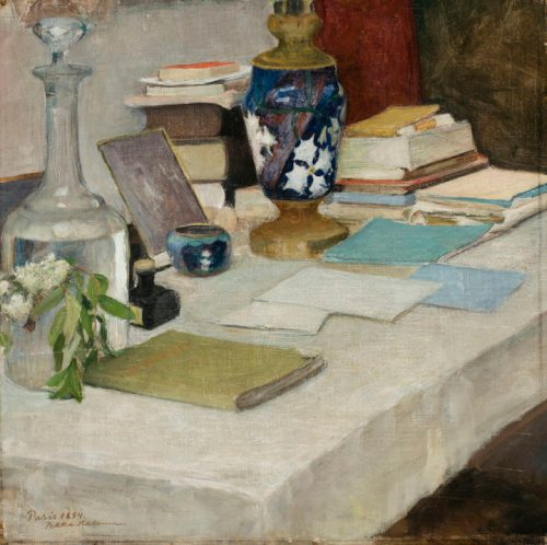 table with white tablecloth used as desk, with notebooks, books, carafe of water and vase