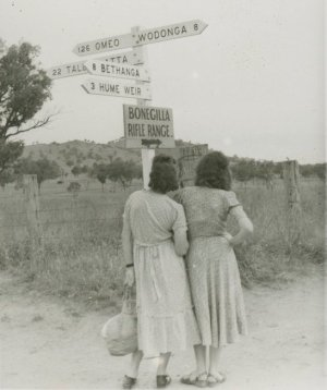 black-and-white photo showing two women with their backs to the camera looking at a signpost on a country road