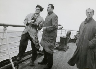 black-and-white photo of three men on the deck of a ship