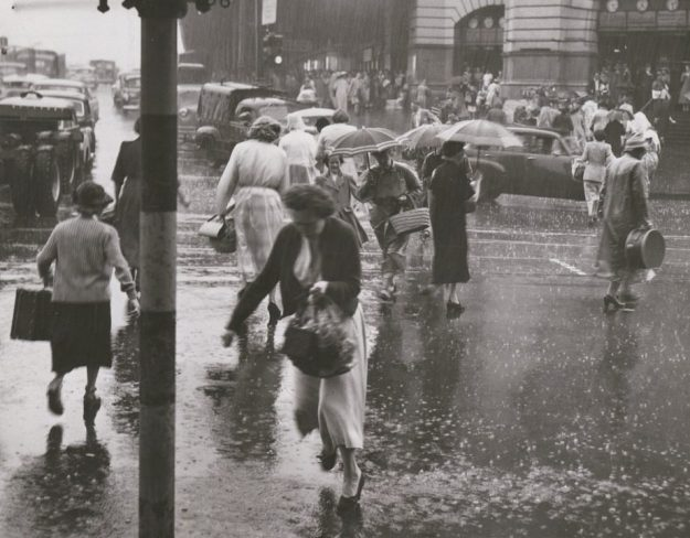 black-and-white photo of women hurrying across a street in rain